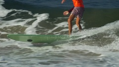 A male surfer rides a wave and wipes out on a longboard surfboard. Stock Footage