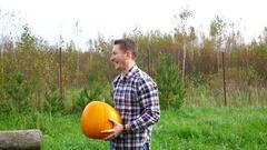 Farmer give laugh while holding big heavy ripe pumpkin, half length portrait Stock Footage
