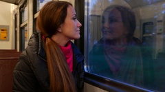Woman travel at suburban train in evening time, look out window and smile Stock Footage