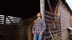 Pleased villager portrait, man stand lean to hayloft doorway and smile Stock Footage