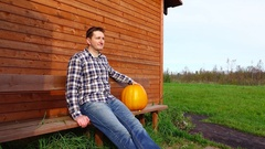 Farmer sit on bench with pumpkin, put it on knee and outline halloween lantern Stock Footage