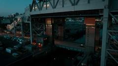 Rising dusk shot of subway travelling on elevated track towards New York City Stock Footage