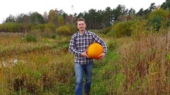 Young adult grower toddle with heavy ripe pumpkin at rural field, dolly shot Stock Footage
