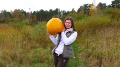 Young adult local girl hold large ripe and vivid pumpkin, pose on camera Stock Footage