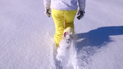Slomo - Below waist shot of a female in ski clothing walking through powder snow Stock Footage