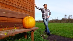 Villager stand against large ripe pumpkin on bench, man take it and go away Stock Footage
