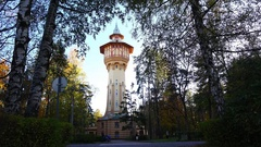 Picturesque water tower seen through opening in dark leafage Stock Footage