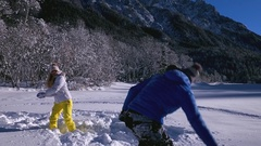 Slow motion - Man tossing woman into the snow during playful snowball fight Arkistovideo