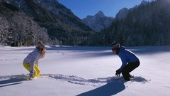 Slow motion - Man grabs and tosses woman into the snow during a snowball fight Arkistovideo