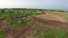 The drone flies over a village near the shore of a lake in West Africa Stock Footage