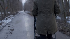 Mother walking down forest path pushing stroller in winter Stock Footage
