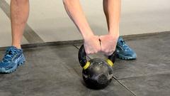 Kettlebell swings by athletic woman, pan. Stock Footage