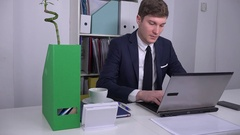 Handsome young businessman working inside white office on laptop confident face Stock Footage