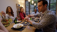 4K Happy group of friends at dinner party raise their drinks for a toast Stock Footage
