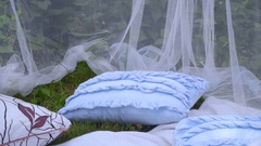 Blue pillows and white transparent fabric at park. Beautiful wedding decor Stock Footage
