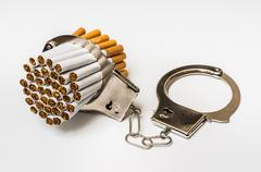 Cigarettes and handcuffs - smoking addiction concept on white background Stock Photos