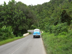 Movement behind blue retro car on the hidhway in tropical jungle mountain Stock Footage