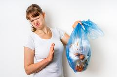 Woman holding a smelly garbage bag isolated on white background Stock Photos