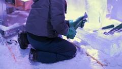 Man carves ice sculpture on knees Stock Footage