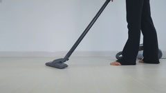 Young attractive housewife vacuuming in the room Stock Footage