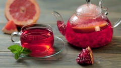 Glass teapot and cup of red tea with grape, pomegranate, mint on a brown wooden Stock Footage