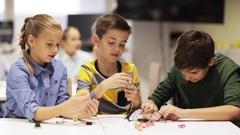 Happy children making high five at robotics school Stock Footage