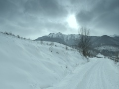 Dark clouds over the high snowy peaks and lawn covered in snow Stock Footage