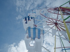 Ferris wheel rotates in the background sky and white clouds Stock Footage