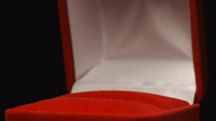 SLOW MOTION: Golden ring falls on a red gift box Stock Footage