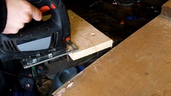 Electric fretsaw is sawing wooden plank in the garage Stock Footage