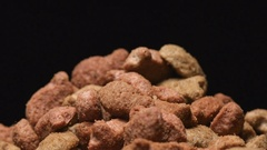 SLOW MOTION: Macro shot of falling of pet food on a heap Stock Footage