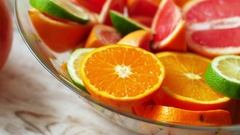 Oranges, limes, tangerines and grapefruit in bowl on wooden background. 4k Stock Footage