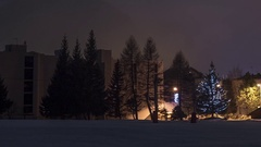 Zoom over snow covered buildings and trees lit by lamps and fog moving Stock Footage