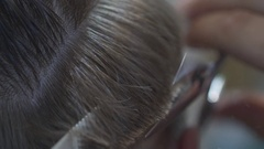Slowmotion with a hairdresser cuts the hair of the client with scissor Stock Footage