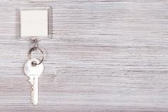 Key with key chain on wooden surface Stock Photos