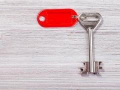 Big door key with red key chain on wooden board Stock Photos