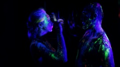 Couple in love painted fluorescent powder dance in ultraviolet light Stock Footage