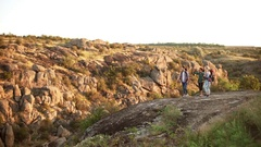 Three friends walking in rocky landscape with camping backpacks giving high five Stock Footage