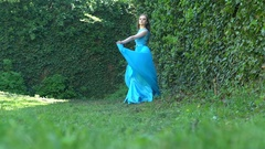 Slow motion: Sexy girl on the background wall with ivy slow waves blue dress Stock Footage