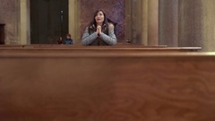 Sad young woman prays desperately in church Stock Footage