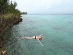 Young slender woman in black swimsuit is lying on the water of caribbean Stock Footage