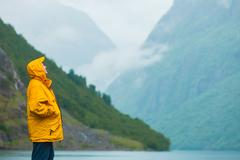 Tourist looking at mountains and fjord Norway, Scandinavia. Stock Photos