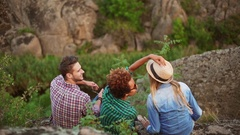 Three friends sitting outdoors talking laughing smiling discussing. One tries on Stock Footage