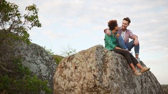 Caucasian male with dark skinned girlfriend sitting on high rock smiling talking Stock Footage