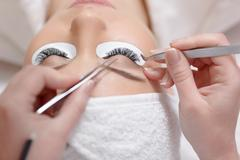 View from above of stylist lengthening lashes Stock Photos