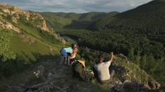 Backpacker family has a rest in a rock mountains Stock Footage