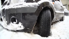 Car stuck in snow with spinning wheel Stock Footage