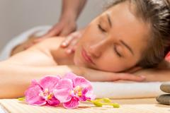 Orchid on a massage table in the spa cabinet and a woman's face Stock Photos