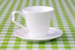 Empty cup on the checkered tablecloth Stock Photos