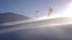 Ski lift moving up to the mountain. Snowboarder crossing over. Stock Footage